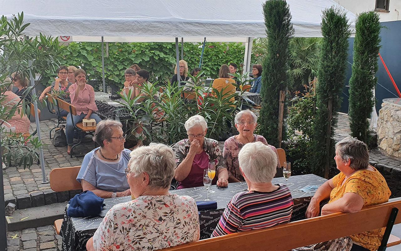 Gruppe von Frauen im Sitzen auf Bänken